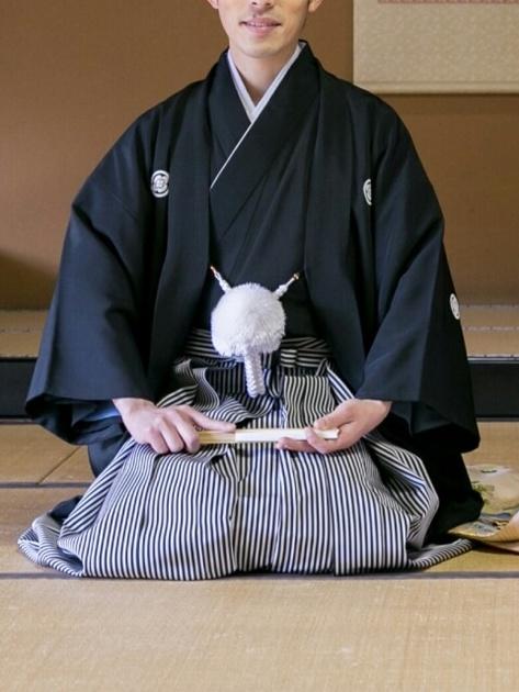 黒色の羽織を着て正座をしている男性