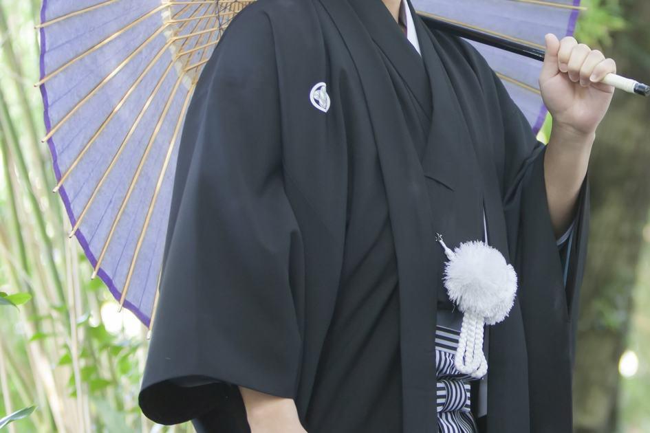 黒色の羽織を着て和傘を持っている男性
